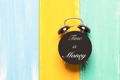 Tempo é dinheiro despertador preto nos fundos coloridos com expressão Tempo é dinheiro Imagem de Stock Royalty Free