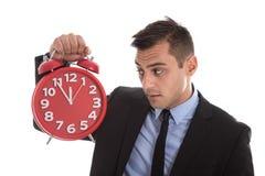 Tempo é dinheiro: homem de negócios que sustenta o despertador vermelho isolado Imagens de Stock Royalty Free