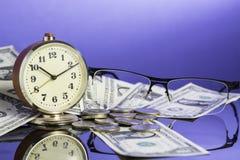 Tempo é dinheiro, pulso de disparo do vintage em notas de dólar americanas do dinheiro, moedas e vidros com fundo azul agradável  Fotografia de Stock Royalty Free