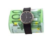 Tempo é dinheiro. Relógio e 100 euro- contas no branco Fotos de Stock