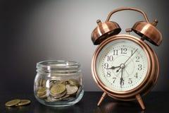 Tempo al concetto di risparmio - stoni il risparmio con il retro orologio sulla b nera fotografie stock