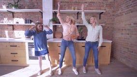 Tempo com mãe, dança alegre da mamã com filhas e divertimento do divertimento ter na cozinha em casa no fim de semana