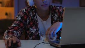 Tempo da despesa do aluno da High School em linha na noite, jogando o jogo de vídeo no portátil filme