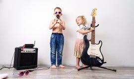 Tempo da família: as crianças, um menino e uma menina, organizam um concerto da casa e para cantar com um microfone e uma guitarr imagem de stock royalty free