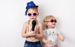 Tempo da família: as crianças, um menino e uma menina, organizam um concerto da casa e para cantar com um microfone e uma guitarr foto de stock