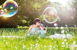 Tempo da família da mãe e da filha, sabão-bolhas de sopro foto de stock