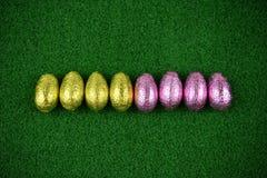 Tempo da Páscoa com os ovos da páscoa envolvidos brilhantes coloridos brilhantes do chocolate em um fundo da primavera da grama v Imagens de Stock Royalty Free