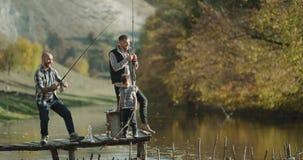Tempo da pesca para dois amigos e um menino pequeno em peixes de travamento do dia ensolarado com vara de pesca 4K video estoque