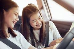 Tempo de férias e curso, cursos alegres das jovens mulheres bonitas junto por um feriado de relaxamento E o riso no carro fotografia de stock