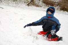 Tempo de inverno. O menino novo senta-se na neve. Imagem de Stock