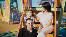 Tempo de lazer feliz da despesa da família junto no campo de jogos no dia de verão Mather, pai e filho sentando-se em escadas de filme
