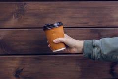 tempo del caffè del ` s! La mano del ` s della donna che tiene la tazza di carta di caffè fresco contro il taleawat di legno scur fotografia stock libera da diritti
