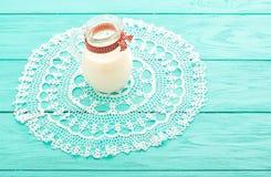 Tempo del pranzo con la brocca di nastro del plaid e del latte su fondo di legno blu Retini la tovaglia Fuoco selettivo Immagini Stock Libere da Diritti