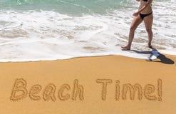 Tempo della spiaggia scritto in sabbia con la giovane donna Fotografie Stock Libere da Diritti
