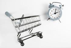 Tempo di acquisto Colore grigio della sveglia e del carrello su un fondo bianco immagine stock