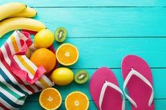 Tempo di divertimento di estate Frutti su fondo di legno blu Arancia, limone, kiwi, frutta della banana in borsa e Flip-flop sul  Fotografia Stock