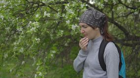 Tempo di fioritura Una giovane donna starnutisce vicino di melo, un'allergia video d archivio