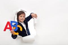 Tempo di imparare - il giovane ragazzo di scuola con le lettere variopinte di alfabeto Immagini Stock