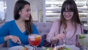Tempo di mangiare, giovani donne comunicare e tagliare insalata con la forcella e coltello in mani durante la dieta in caffè archivi video