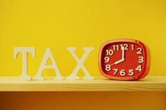 Tempo di pagare le lettere e la sveglia di alfabeto di imposta di concetto di imposta fotografie stock libere da diritti