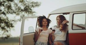 Tempo di picnic di due giovani donne, vino bevente e condizione accanto al retro bus, capelli ricci, buon umore stock footage