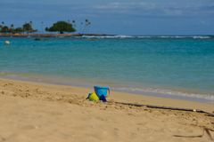 Tempo di vacanza, un secchiello e paletta che mette su una spiaggia immagine stock libera da diritti