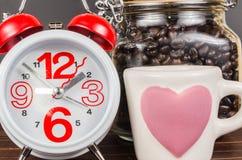Tempo do café, despertador com o copo de café branco e feijão de café dentro Fotografia de Stock Royalty Free