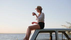 Tempo do chá para a fêmea nova no automóvel do vintage na terraplenagem perto do mar, xícara de café à disposição da menina vídeos de arquivo