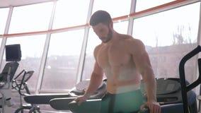 Tempo do esporte, o homem forte considerável do atleta faz o aquecimento após o treinamento da força no músculo da construção no  filme