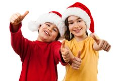 Tempo do Natal - menina e menino com Santa Claus Hat que mostra o sinal APROVADO Imagem de Stock