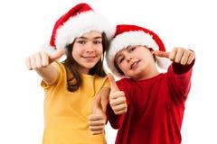 Tempo do Natal - menina e menino com Santa Claus Hat que mostra o sinal APROVADO Imagens de Stock