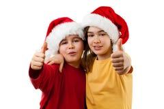 Tempo do Natal - menina e menino com Santa Claus Hat que mostra o sinal APROVADO Fotografia de Stock