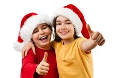 Tempo do Natal - menina e menino com Santa Claus Hat que mostra o sinal APROVADO Fotos de Stock Royalty Free
