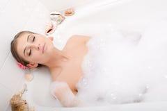 Tempo dos termas: encontro de relaxamento da senhora elegante bonita em uma banheira com espuma com o retrato fechado dos olhos Imagem de Stock Royalty Free