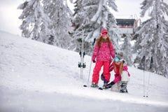 Tempo e esqui de inverno - sira de mãe a preparar a filha na estância de esqui Imagem de Stock