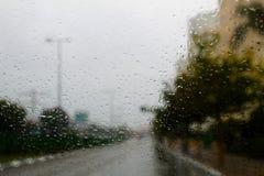 Tempo em Israel: Chuvas do inverno Vista abstrata à cidade chuvosa da estrada através do para-brisas do carro fotografia de stock