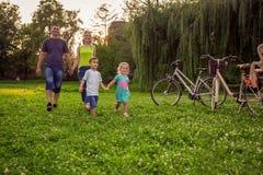 Tempo engraçado - crianças que andam com pais no parque fotografia de stock royalty free