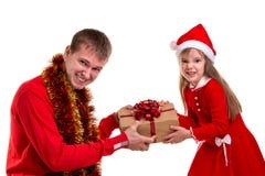Tempo engraçado do xmas da careta da família Filha e pai que vestem chapéus e ouropel de Santa em torno do pescoço Luta pelo pres imagem de stock royalty free