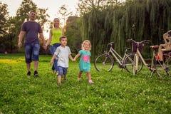 Tempo engraçado - os pares novos com suas crianças têm o divertimento no parque bonito exterior na natureza foto de stock