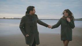 Tempo ensolarado em um bom humor Um par loving está correndo ao longo da água na areia Estão no amor e feliz Homem video estoque