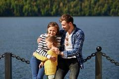 Tempo feliz da despesa da família junto fora perto do lago Pais que jogam com a filha que abraça e que tem o divertimento fotografia de stock