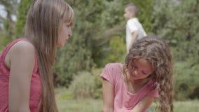 Tempo feliz da despesa da família no jardim junto Mãe e filha que comem cerejas no primeiro plano O filho video estoque
