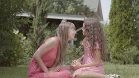 Tempo feliz da despesa da família no jardim junto Mãe e filha que sentam-se no primeiro plano, espirrar da criança filme