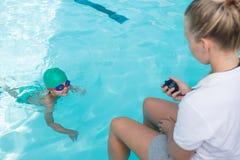 Tempo femminile del monitoraggio dell'istruttore di nuoto del ragazzo nello stagno Fotografie Stock