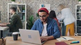 Tempo-lapso do indivíduo ocupado que usa o portátil nos colegas do quando do escritório que apressam-se ao redor vídeos de arquivo
