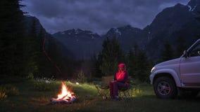 Tempo-lapso dos pares que conversam pela fogueira no acampamento no vale da montanha Por do sol vídeos de arquivo