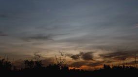 tempo-lapso 4K que mostra um nascer do sol alaranjado bonito sobre o campo e as árvores Cores dramáticas bonitas das nuvens Noite filme