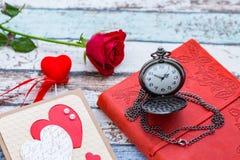 Tempo per amore: rosa rossa, cuore e giornale con l'orologio da tasca Fotografie Stock