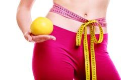 Tempo per il dimagramento di dieta. Nastro della donna intorno alla frutta del corpo a disposizione Fotografia Stock Libera da Diritti