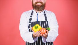 Tempo per il pranzo Cuoco barbuto dell'uomo in cucina, culinaria vegetariano Cuoco unico maturo con la barba Cottura sana dell'al fotografia stock libera da diritti